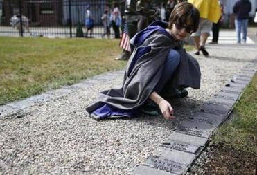 Emma Bibbins, 15, of Medford, placed a stone atop a marker bearing a child's name; people entered the grounds; and a stone commemorated a baby's short life .